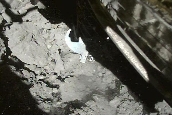 Sonda Hayabusa 2 v momente pristátia na asteroide Rjugu.