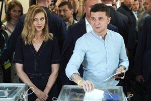 Ukrajinský prezident Volodymyr Zelenskyj vpravo a jeho manželka Olena hádžu volebné lístky do volebnej urny vo volebnej miestnosti v ukrajinskom Kyjeve 21. júla 2019.