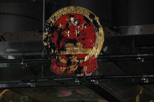 Štátny symbol Číny nachádzajúci sa nad vchodom do budovy postriekali čiernym atramentom.