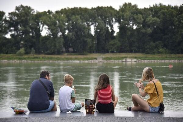 Ľudia odpočívajú na nábreží Dunaja počas horúceho letného dňa.