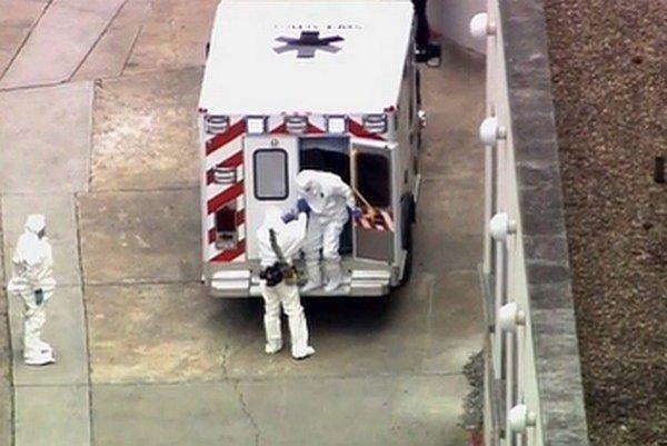 Americký lekár Kent Brantly (vpravo) nakazený vírusom eboly vystupuje zo sanitky pred Emoryho univerzitnou nemocnicou v Atlante.