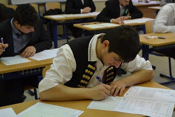 Martin počas písomných maturít. Spolužiaci v oblekoch, on v kroji.