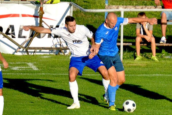 Hosťujúci Milan Patka z Kľúčového (v modrom) v súboji o loptu s Adamom Moravčík v zápase Veľké Bierovce/Opatovce - Kľúčové 0:0.
