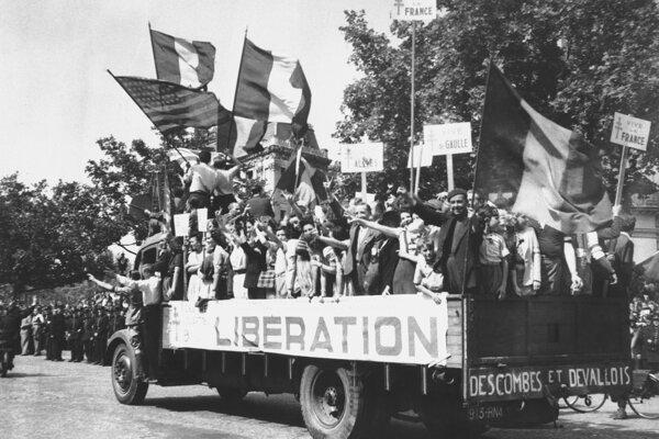 Na archívnej snímke z 28. augusta 1944 nákladné auto vezie Parížanov, ktorí mávajú vlajkami a transparentmi s nápisom Nech žije De Gaulle po oslobodení Paríža.