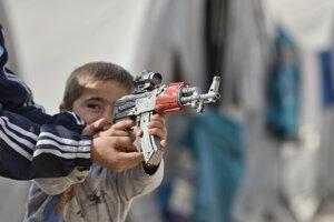 Ilustračné foto – chlapec sa hrá s detskou puškou v utečeneckom tábore v Sýrii.