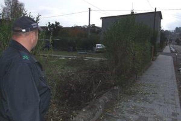 Mestský policajt pozerá na poškodený plot, v pozadí auto, ktoré havarovalo.