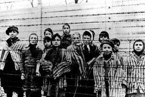 Na archívnej snímke z januára 1945 obete fašistického holokaustu - deti stoja za ostnatým drôtom v nacistickom koncentračnom  tábore v poľskom Osvienčime tesne po tom, ako tábor oslobodili sovietske jednotky.