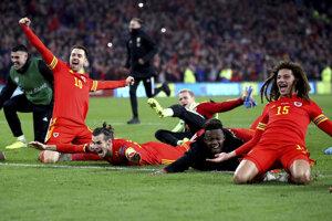 Gareth Bale (na zemi v strede) oslavuje postup na EURO.