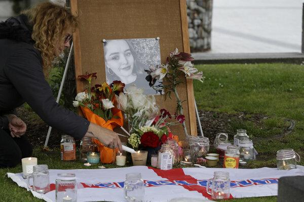 Žena zapaľuje sviečku pre zabitú turistku Grace Millaneovú.