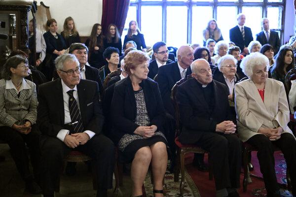 Ocenení seniori a hostia sledujú slávnostné oceňovanie.