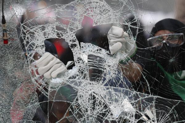 Maskovaní demonštranti rozbíjajú sklo reklamného billboardu počas protestu proti násiliu páchanému na ženách. Mexiko, 25. november 2019.