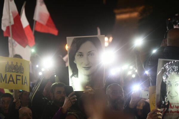 Demonštranti pred kanceláriou premiéra držia fotografie zavraždenej novinárky.