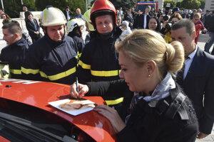 Ministerka vnútra Denisa Saková podpisuje fotografiu hasičom z obce Tehla, ktorým odovzdala nové zásahové vozidlá v októbri 2019.