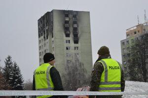 Sobota ráno. Požiar je uhasený, okolie bytovky stráži polícia a vojaci.