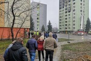 Evakuovaní obyvatelia vchodu číslo 5 čakajú, kým ich pustia na nevyhnutný čas na zabezpečenie do bytov.