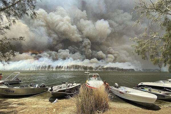 Člny sú priviazané na brehu jazera v malom meste Lake Conjola počas lesných požiarov v austrálskom štáte Nový Južný Wales.