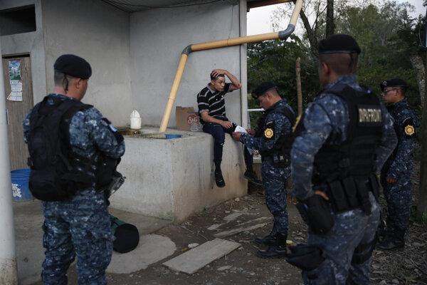 Guatemalská polícia kontroluje utečenca.