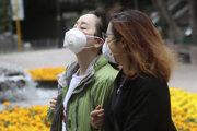 Ľudia s maskami v meste Hongkong.