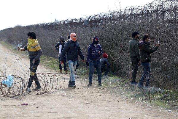 Migranti sa snažia prekonať bariéru pri hraniciach Turecka s Bulharskom v Edirne.