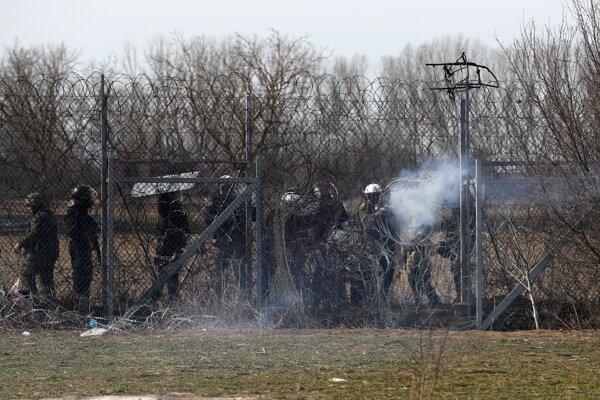 Príslušníci gréckej poriadkovej polície zasahujú voči migrantom, ktorí sa pokúšajú vstúpiť na územie Grécka slzotvorným plynom počas zrážok v dedine Edirne na turecko-gréckej hranici Pazarakule 2. marca 2020.