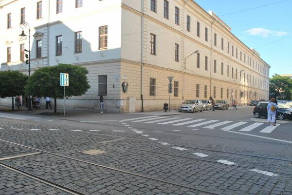 Križovatka. Cyklistka prichádzala zľava (po Hlavnej ulici), nákladniak vychádzal z vedľajšej ulice (Kasárenské námestie) a odbočil vpravo.