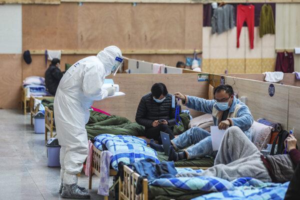 Lekár pri kontrole pacientov v dočasnej nemocnici v čínskom meste Wuchan 21. februára 2020.