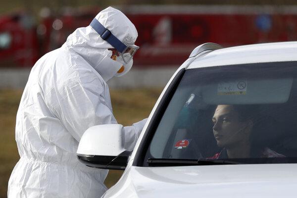Zdravotník v ochrannom odeve meria teplotu cestujúcej v automobile na hraničnom priechode Českej republiky s Nemeckom v Rozvadove v pondelok 9. marca 2020.