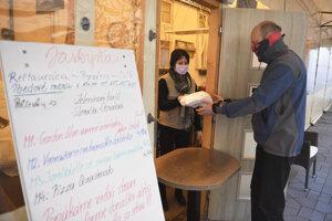 Čašníčka vydáva zabalený obed z reštaurácie zákazníkovi v centre Košíc kvôli zatvoreným reštauráciam.