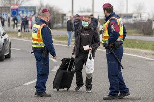 Policajti kontrolujú cudzincovi doklady na uzavretom rakúsko-maďarskom hraničnom priechode pri Hegyeshalome.