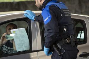 Člen švajčiarskej pohraničnej stráže kontroluje francúzskeho občana na švajčiarsko-francúzskej hranici vo švajčiarskom Vallorbe.