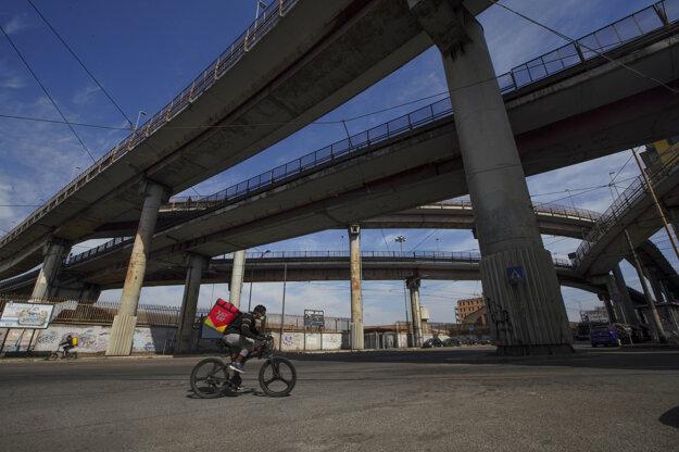 Doručovateľ jedla jazdí na bicykli po prázdnych uliciach v Ríme v Taliansku.