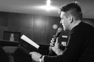 Peter Balko číta uážku zo svojej knihy na multižánrovom festivale Medzihmla.
