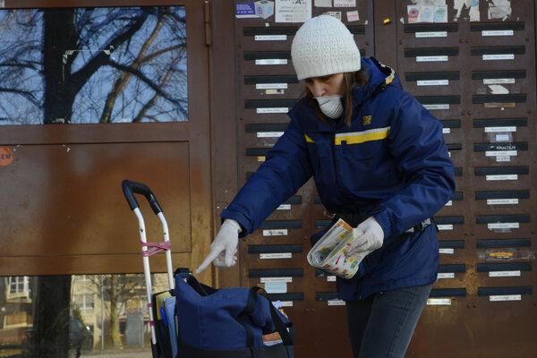 Poštová doručovateľka roznáša zásielky v gumených rukaviciach a s ochranou nosa.