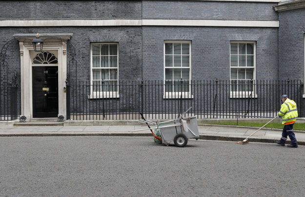 Zametač čistí krajnicu pred sídlom britského premiéra na Downing Street 10 v Londýne.