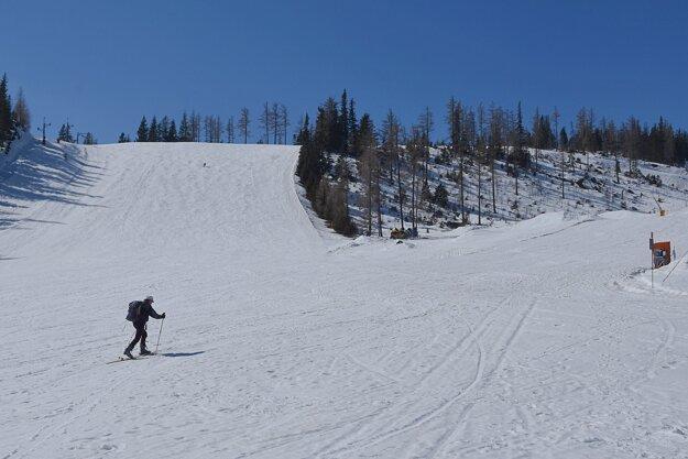 Skialpinista kráča po prázdnej zjadovke Interski na Štrbskom Plese vo Vysokých Tatrách.