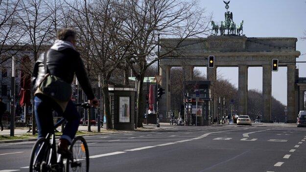 Cyklista ide po takmer prázdnej ceste, ktorá vedie k Brandenburskej bráne v Berlíne.