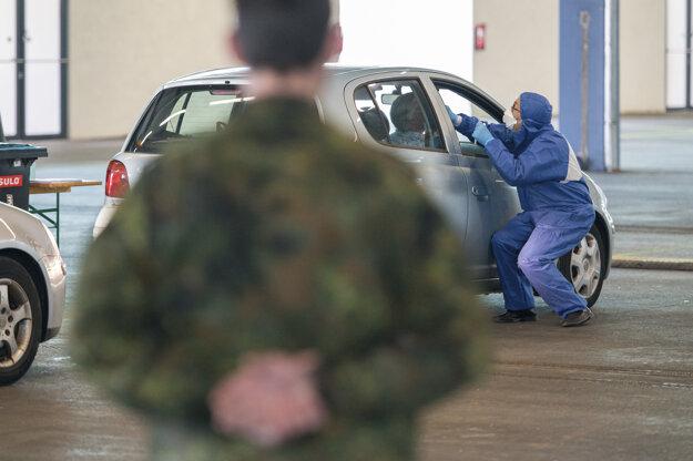 Doktor počas mobilného testovania ľudí čakajúcich v aute pri takzvanom drive-thru teste na nový koronavírus.