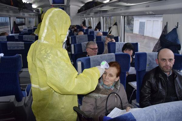 Na snímke z 20. marca meria ukrajinský zdravotník teplotu cestujúcim v autobuse na poľsko-ukrajinskej hranici.