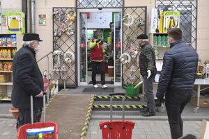 Ľudia čakajú v rade pred predajňou pre záhradkárov v Košiciach.