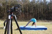 Mladá gymnastka trénuje pod dozorom trénera on-line.