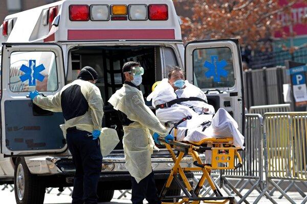 Zdravotníci v ochranných odevoch privážajú pacienta s ochorením COVID-19 do zdravotníckeho zariadenia Elmhurst Hospital Center v New Yorku.