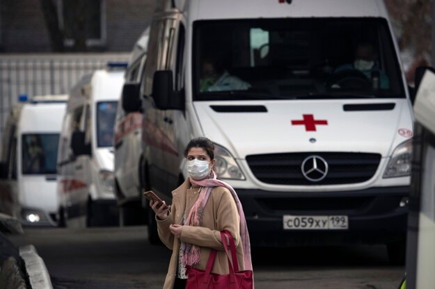 Žena s ochranným rúškom na tvári kráča okolo sanitiek, ktoré privážajú pacientov podozrivých na ochorenie COVID-19 do nemocnice v Moskve.