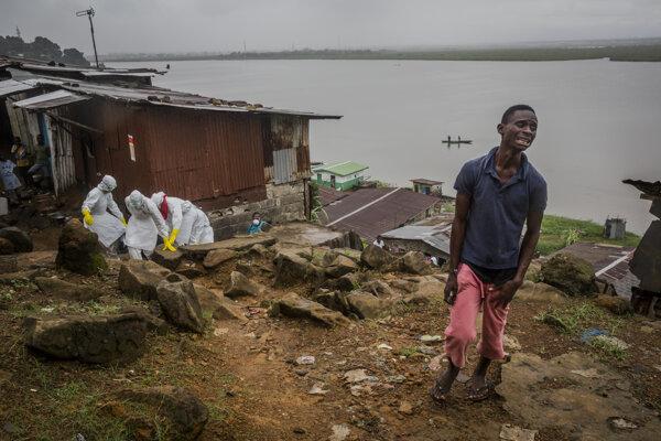 Pracovníci Červeného kríža vynášajú zosnulého. Muž v popredí oplakáva smrť otca, ktorého zabila ebola. Záber vznikol 20. apríla 2015 v libérijskej Monrovii. Pochádza zo série fotografií ocenenej Pulitzerovou cenou.