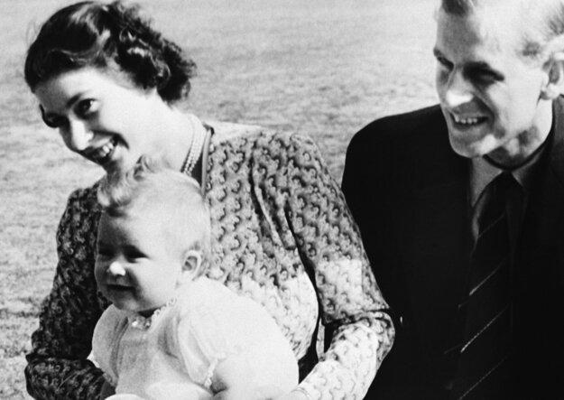 Na snímke z 18. júla 1949 osemmesačný britský princ Charles, jeho matka Alžbeta a jeho otec Philip pózujú v letnej rezidencii v Ascote.