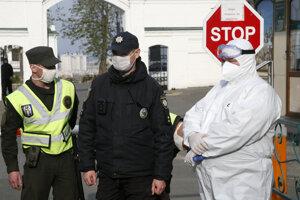 Policajti v ochranných rúškach blokujú cestu do pravoslávneho kláštorného komplexu v Kyjeve.