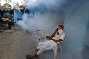 Postarší Ind si zakrýva tvár zatiaľ čo miestny pracovník vydymuje časť mesta Iláhábád, aby zabránil šíreniu nového koronavírusu.