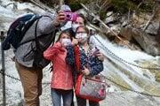 Turisti v ochranných rúškach sa fotografujú pri vodopádoch Studeného potoka vo Vysokých Tatrách.