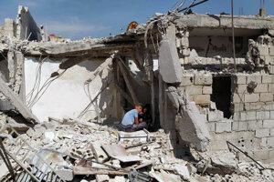 Chlapci sedia v troskách domu po raketovom útoku izraelských vzdušných síl na predmestí Hadžíra v sýrskom Damasku.