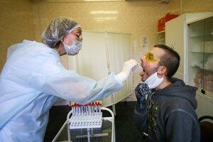 Zdravotná sestra robí pacientovi výter z hrdla počas testu na ochorenie COVID-19 v Moskve 15. mája 2020.