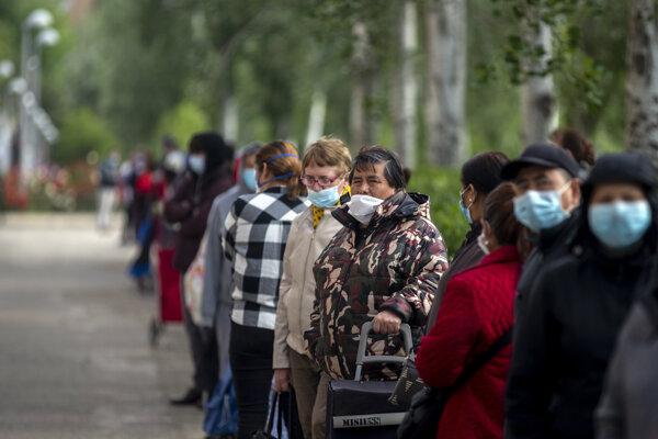 Ĺudia s rúškami čakajú v rade na prídel jedla v Madride.